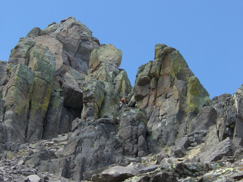 Summit block of Dallas Pk with car-sized chockstone beneath.  Climber can be seen in the 4th class gully (right of chockstone) which leads to the north side class 5.3 summit pitch (Aug. 1, 2009).