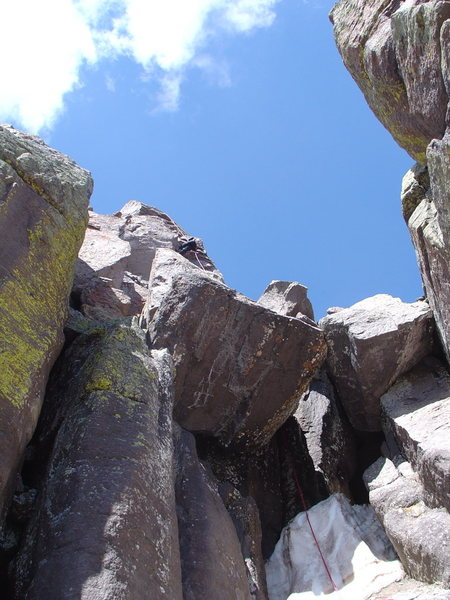 Rapping off the east side of the summit block through the hole beneath the chockstone (Aug. 1, 2009).