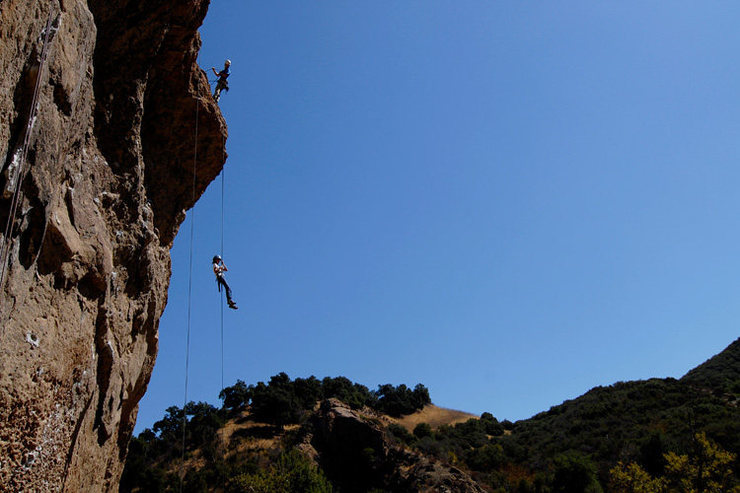 The Planet of the Apes Wall, with a local school group rappelling from the summit.
