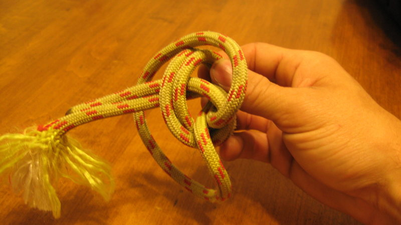 Bringing the loop from my wrist over the knot, continuing to hold the same two strands of rope.