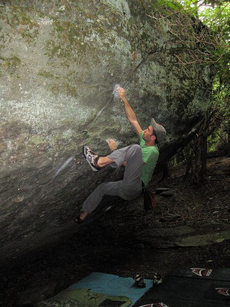 "Aaron James Parlier with his left hand on the start, right hand in the jug crack, climbing ""Static Crack"" at the Olympus boulder in Grayson Highlands State Park, VA"