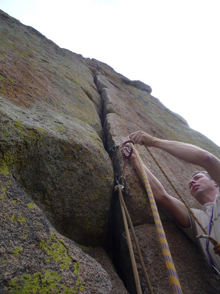 Looking up the crack and clipping the first piece.