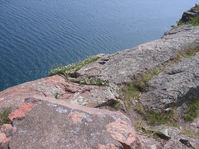 the top-out/top-rope anchor location is located just to the right/south of the stone lookout wall (you can see it in the left-hand side of the photo).