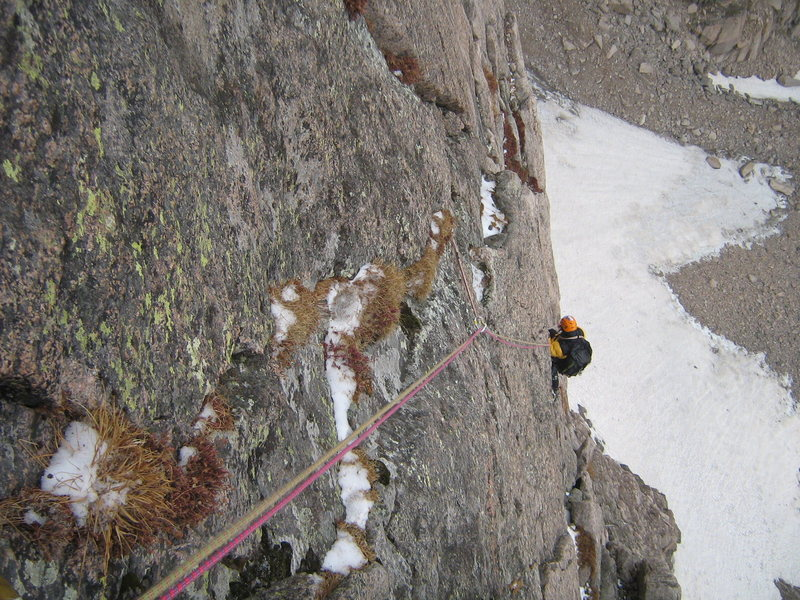 Jesse cleaning some gear on the upper flakes of Malander's Passage, after several late September snow squalls coated the wall quite nicely in white stuff and wet.