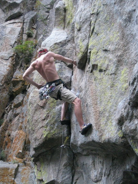 Plugging in some gear at the end of the crux.