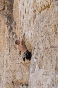 trying to pull the roof move on a short route labeled 5.12a in chalk