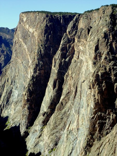 The route follows the sun/shade line on the far right side of the Porcelain Arete buttress.