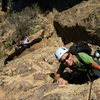 """Francine Beattie climbs Rational Expectations, at the Fortress, as Audrey Walzer relaxes on """"lunch ledge."""""""