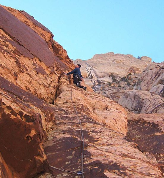 On the uppermost pitch, contemplating the traverse.