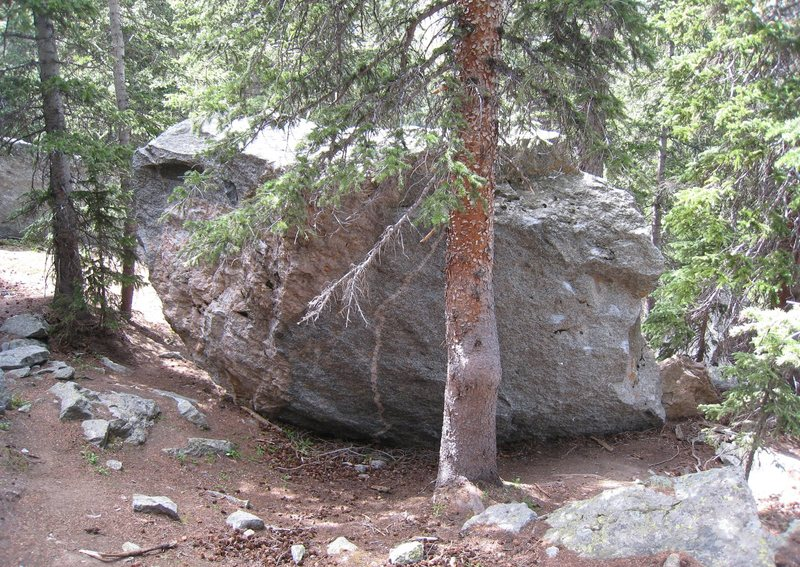 In the woods uphill from Seurat/Chocolate Croissant.  This boulder might have more than one problem on it.