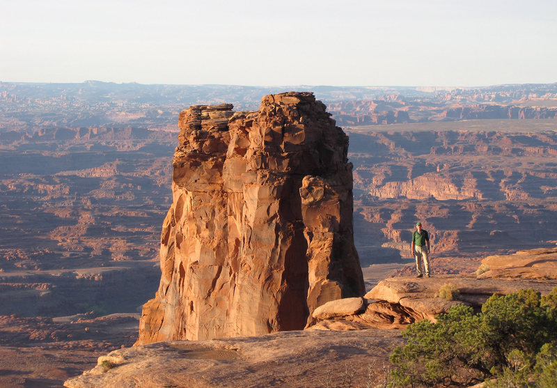 Ben Kiessel standing on the rim near the Canyonlands Overlook rappels.<br> <br> Attila's Thumb is visible in the background as the sunlight column in front of Mitten Butte.