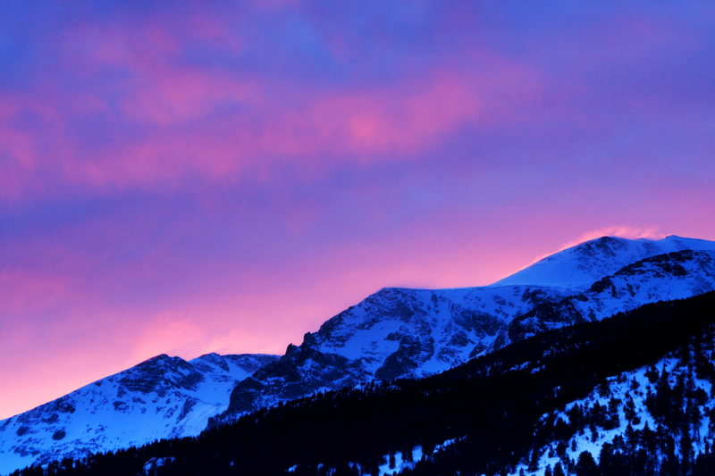 Spindrift lit with alpenglow high on a ridge in Rocky Mountain National Park.