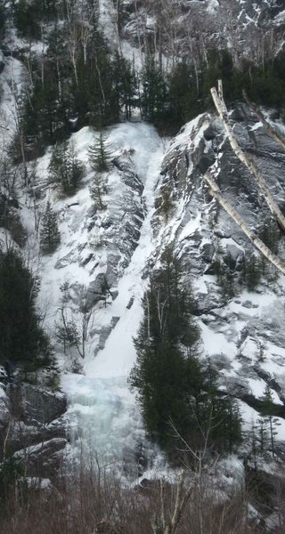 <em>Crystal Ice Tower</em> at the bottom. <em>White Line Fever</em> is its continuation, running up the snow chute through a narrow ice band, with yet another pitch above the belt of trees.