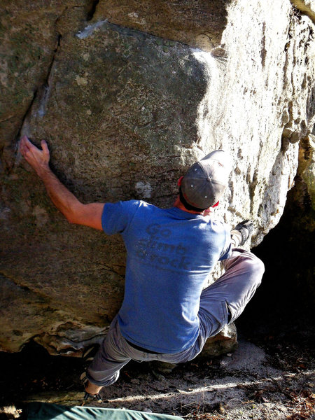 "Aaron Parlier with his hand in the left slot and a hand foot match on the right side finger rail on ""Maxima""(v-5/6). Maxima Boulder. Bluefield."