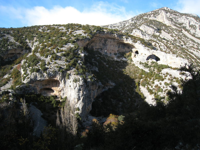 """Criminal Tango"" is the orange double-cave on the left, the right, shaded side of the gray buttress just left of center is ""Aquest Any Si"", and the big cave at the top is ""Las Ventanas"".  The arch on the right is ""El Delfin""."
