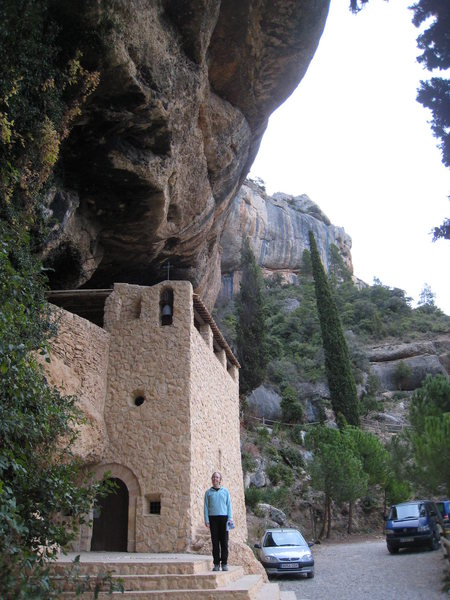 """The """"Ermita Sant Salvador"""" shrine, built into the cliff, is a good rest day destination, located at the top of the small canyon that hosts the Finestra, Tenebres, & Cabernet crags.  The Cabernet cliff is in the background."""
