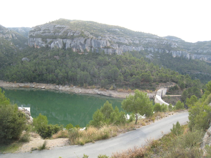 "The ""Embassement"".  There is free camping below the damn.  The large cliff just left of center is ""Ca La Morta"" (with 30 or so routes 12a & under).  ""Culampe 4"", home to one of Margalef's best 12a's, is the largest block on the right."