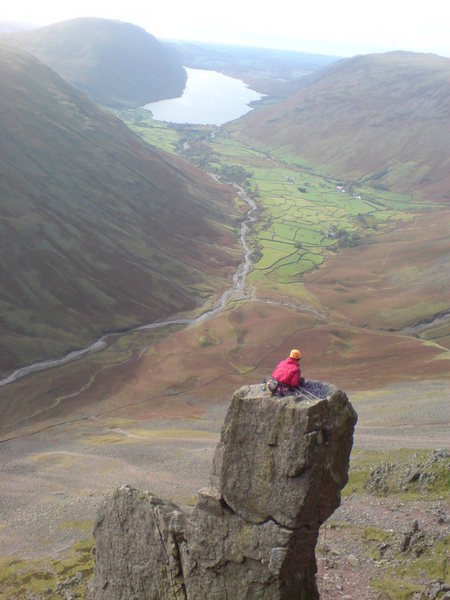 Climber on the summit block of the Needle with a view down the Wasdale Valley.photo Chris Cooper