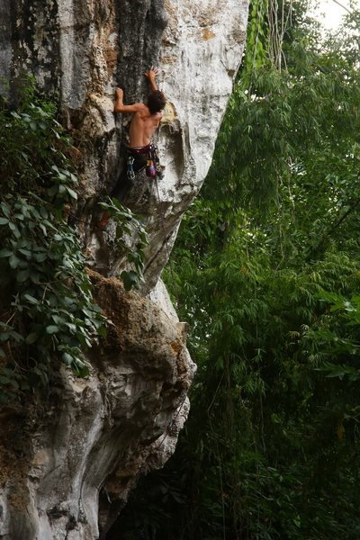 Martin getting to the slippery tuffa on Welcome to the Jungle (5.11+).  Vang Vieng, Laos.