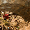 Resting up on the jug at the apex of the cave, Ben prepares to get Full Penetration.