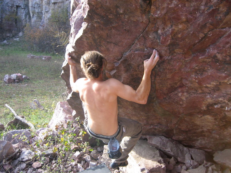 Low on the hard line (SE arete) on the Quarry boulder. (2007)