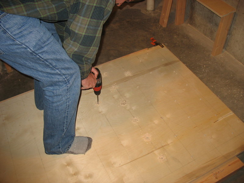 Us drilling holes in the plywood