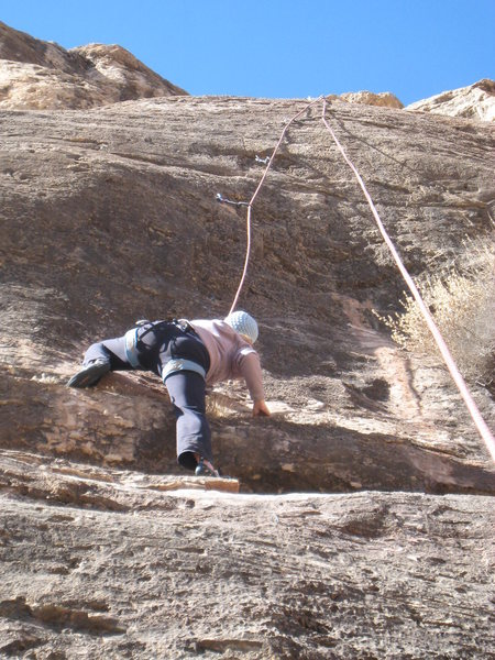 Surmounting a low bulge.  The crux hits with a vengeance at the second draw above the climber.