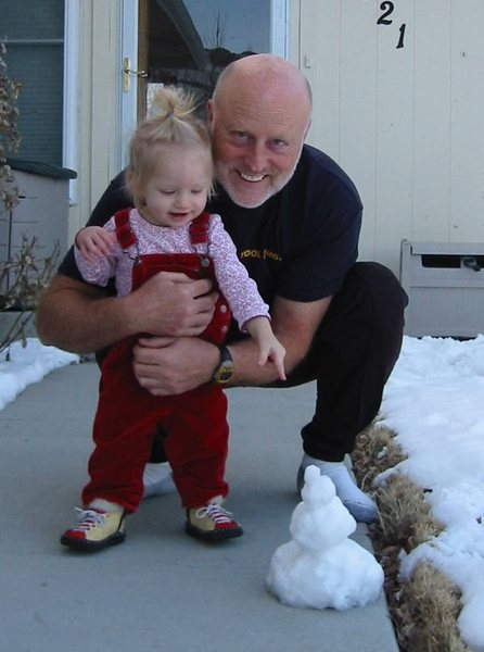 Grandpa making Natalie a snowman.