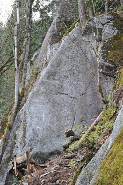 Starts on the thin face crack, traverses left to the arete where the angle kicks back. The direct start is 'Midget Love', 5.12.