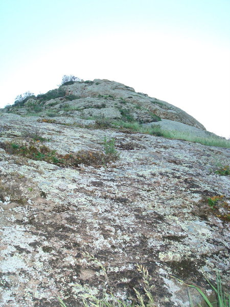 View of Eat Mo' Possum from the top of Shadow Rock. The route ascends slabs to the base of an overhang which is bypassed to the right.