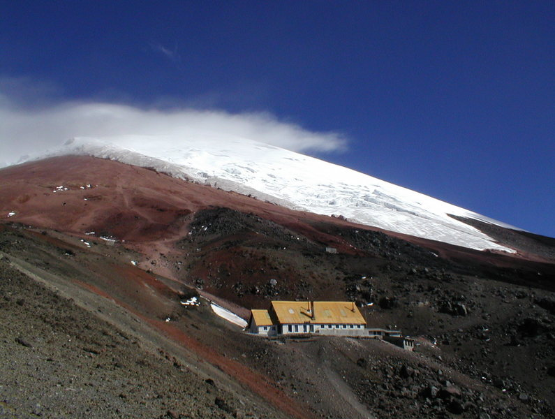 Approaching the José Ribas Hut on Cotopaxi, Ecuador. Several foot paths can be seen in the red volcanic scree that lead to the glacier above.