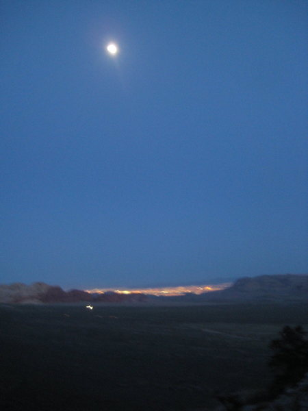 full moon coming up over Red Rocks, NV and the Las Vegas strip