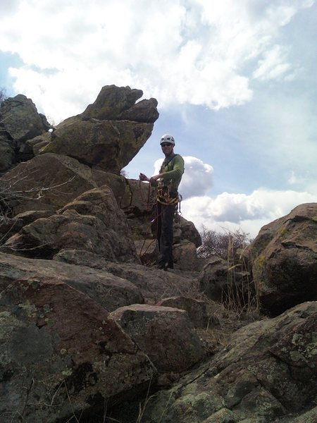 At the top of the original route.  The cedar tree and bolts are a quick scramble over the rocks toward the cross (up canyon). TJ cleans some anchor gear. There is a great rock to wrap a cordolette or webbing around and several cracks for cams or nuts for the anchor.