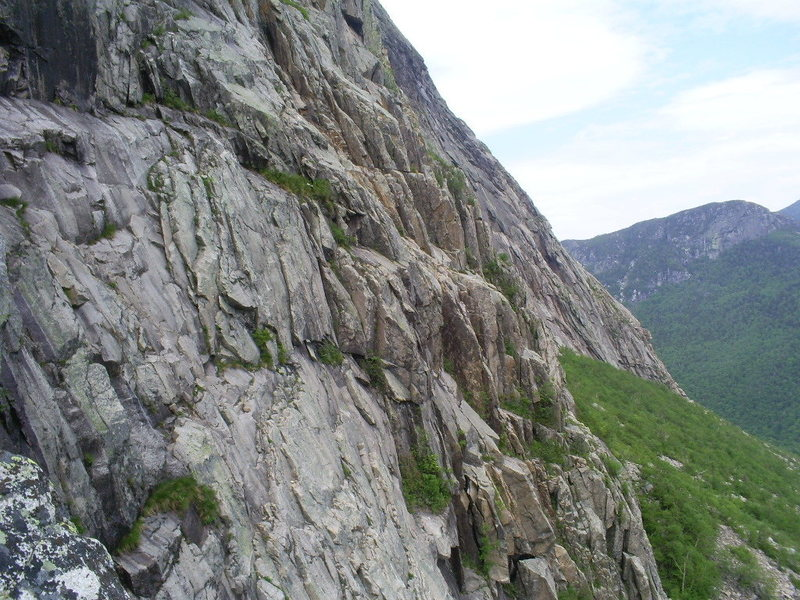 To the right of the bushes in the foreground is 'The Odessa Steps (often wet)' To the right of that is Bull Dog on the crest of the greenish ledges heading towards the second group of bushes. Left of those bushes is a corner. Ascend the outside of the corner up to the smallest dark rock and bushes. The large rock in the corner is now gone. There are variations to be had, including the corner now to be climbed.