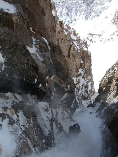 Looking down from the crux, Bill Duncan experiencing the gully in heavy spindrift.