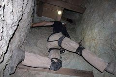 Climbing a vertical shaft in the Waterloo Mine, to access a small opening.