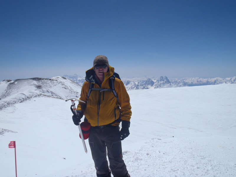 Me on the summit with the crater rim and a small looking Ushba in the background