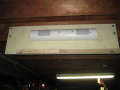 Homemade hangboard with a full pad crimp, half pad crimp, and a big sloper made of PVC reinforced with a trimmed 2x4.