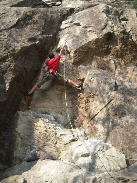 Clipping the second bolt on Justice before moving into the crux.