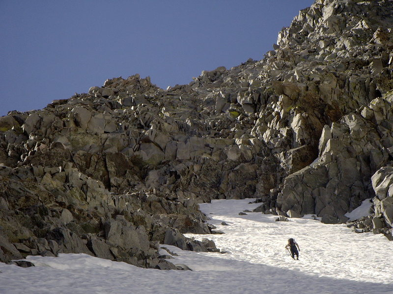 Climbing out of the glacial bowl. The loose rock band above separates the glacier from the L-shaped col.
