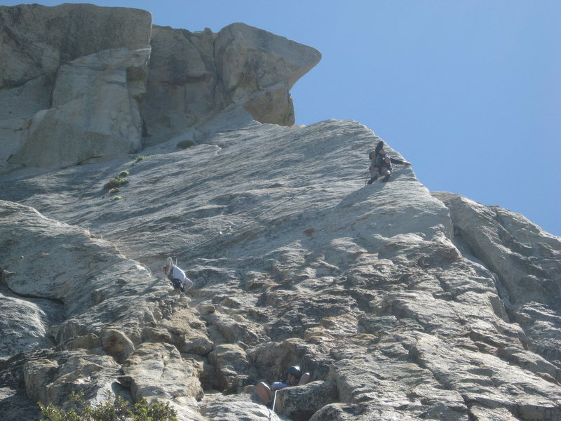 Agina setting up a belay on pitch 1 with climbers on the edge route above her.  6-26-10