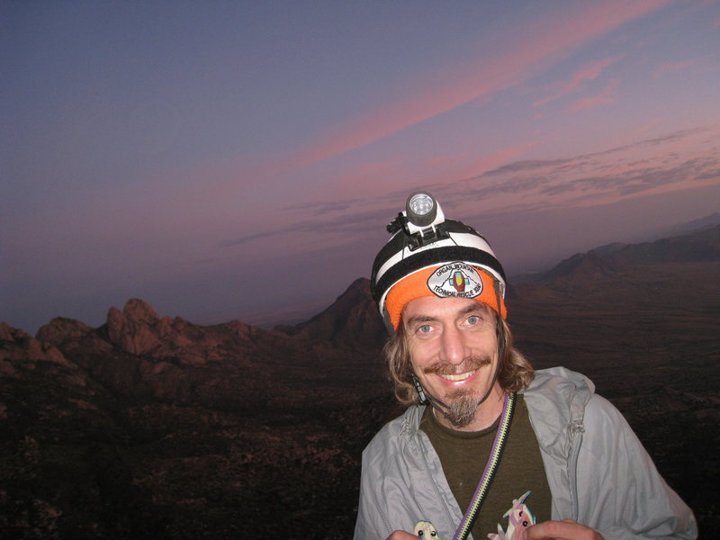 Bob A. as the sun rises near the end of our full moon climb, Sept 5-6, 2009.  (pitch 10 belay?)