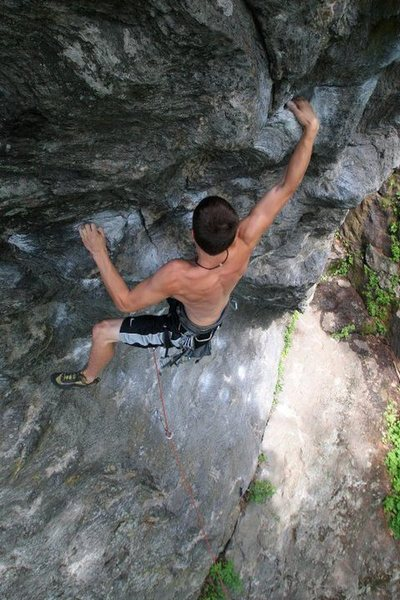 Kevin latching the jug on the lower boulder problem
