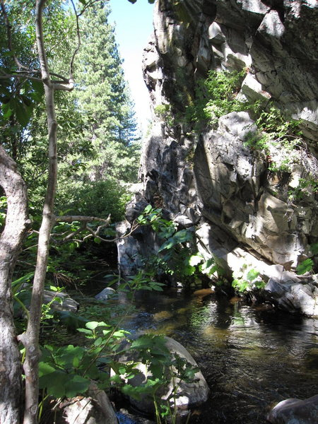 The stream runs around the corner and the last routes on the far left of the crag climb over the top of the water.