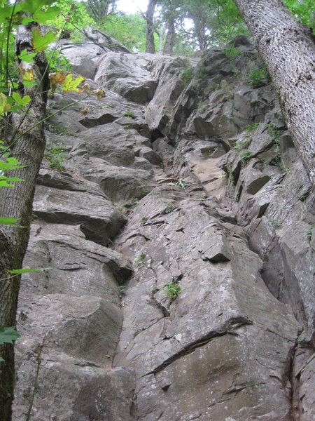 This route is just to the left of the obvious crack called Happy Crake and finishes via the upper part of Happy Crake.