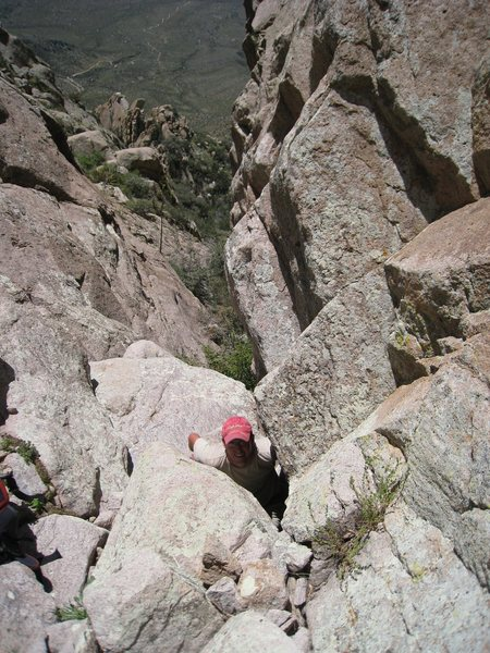 "Zack coming out of the ""birthing hole"" at the top of the ""roofed chimney"" in the gully to gain the P1 belay ledge."