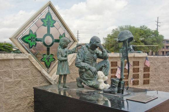 4th ID commissioned statue of remembrance. <br> <br> Depicts Iraqi child thanking a US soldier for liberating the country from Saddam. <br> <br> The materials used were from Saddam statues, as well as the artisan, but disputed Iraqi artisan stated it was all about the money for him as to its purpose.
