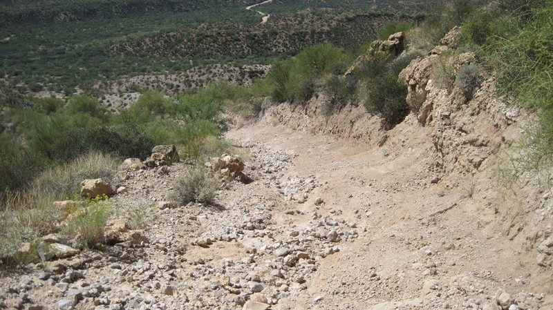 View down from crux showing drainage continuing on road. Rains have washed away fines leaving loose cobble size stones in rut on steep grade.<br>