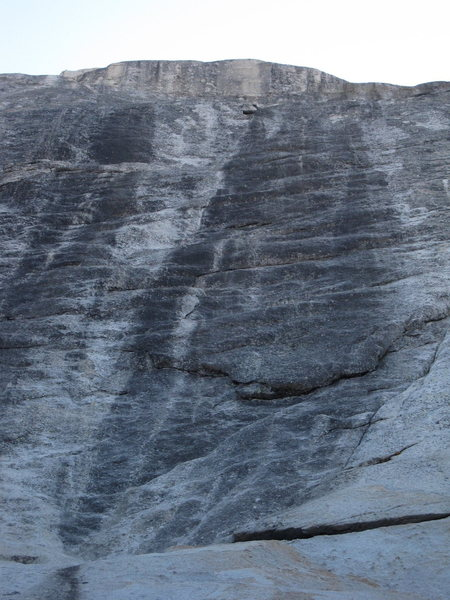 In this photo you can see (in the order they are described in the description): the right leaning ramp; the downward pointing flake; first right facing flake (in white rock to the immediate right of the prominent black streak); second left facing flake (in the black streak); and the white area. You then head up and right to the first bolt.