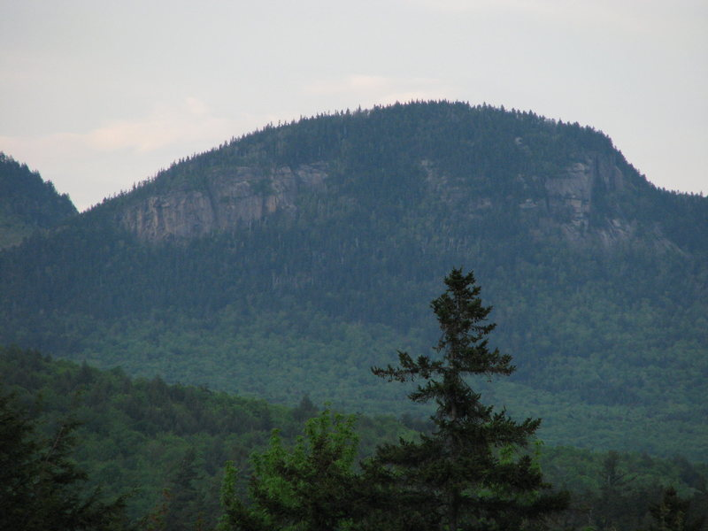 "A blurry long range overview from the Kancamagus Highway of the two main cliffs of Owl's. The left cliff can be seen well, but the right one is facing off to the right, especially the impresssive and badly sandbag named ""5.10 Wall"", seen on edge."